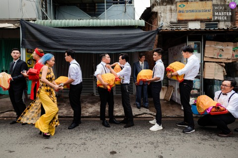 Ho Chi Minh Vietnam wedding photography of the men lined up on the street holding gifts
