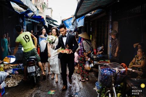 Ho Chi Minh-huwelijksfotografie van de bruid en bruidegom die door een drukke straatmarkt lopen