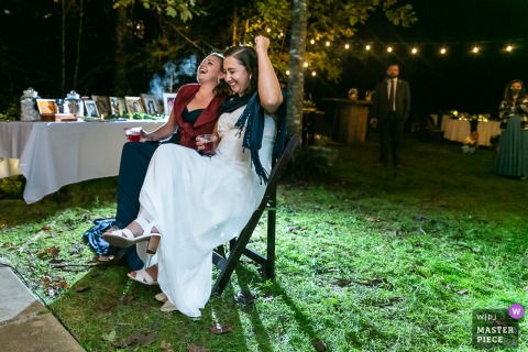 Wedding photography from Wit's End, Ellijay, GA of the Brides reacting to a toast from a distance