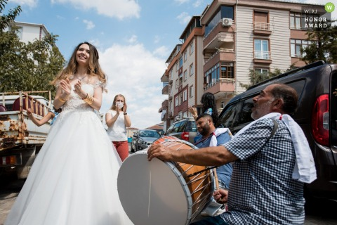 Turkey wedding reportage image from Luleburgaz of the bride dancing on the street as a man plays a drum