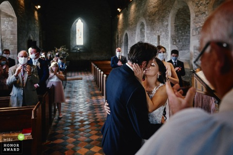 UK wedding photography from All Saints Church, Preston Bagot of the Bride and groom's first kiss during the ceremony