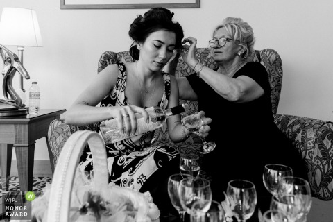 Turkey wedding photo from Izmir showing the Mum Always cares as she fixes the brides hair while pouring drinks at getting ready