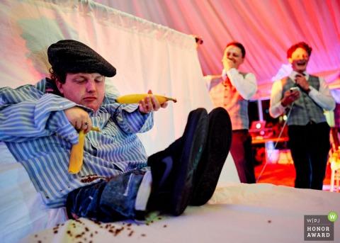 Photo de reportage de mariage en Irlande lors d'une réception au château de Kinnity de The Bride & Groom où elle a été conçue pour faire équipe dans ce jeu amusant. La mariée est derrière le rideau et utilise ses mains comme si elles étaient les mariés pour accomplir des tâches aléatoires