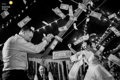 The newlywed couple dances as wedding guests throw dollar bills in the air at their home in Boiling Springs, PA