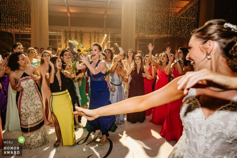 Wedding photography from Marco Luigi as the Bride Throws the Bouquet straight at her friend during the reception party