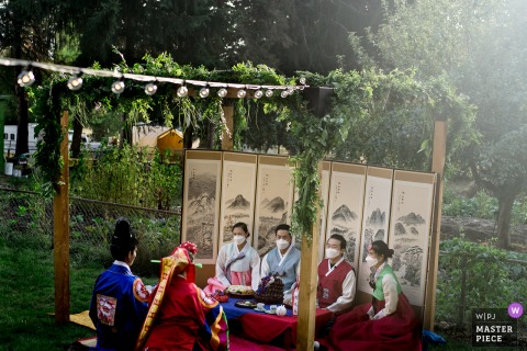 Backyard wedding image of the bride's siblings sharing well wishes during a Korean ceremony