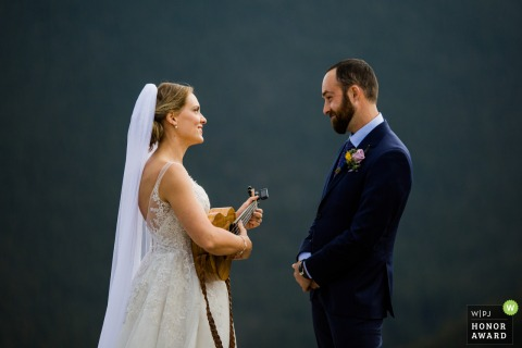 Image of a Denver Colorado Bride playing a song for the Groom at their wedding ceremony