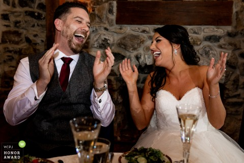 PA wedding photography from Philadelphia, Pennsylvania showing The bride and groom laughing during the toasts at their wedding reception venue