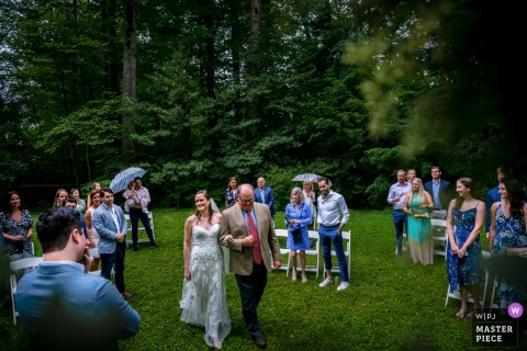 The bride is escorted down the aisle by her father, perspective is from the officiant, the groom holds his hand over his face in awe at their Falls Church, Virginia backyard wedding