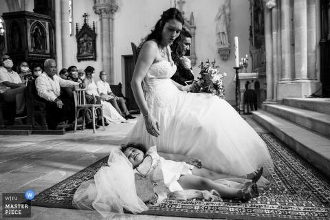 Immagine del matrimonio della Chiesa di Gondrecourt della figlia della sposa che posa sul suo vestito durante la cerimonia