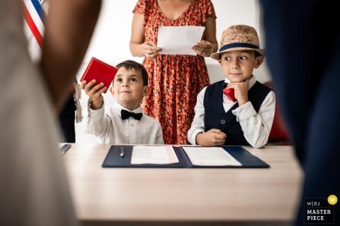 Due figli aspettano pazientemente e pronti a consegnare le fedi ai loro genitori durante una cerimonia in municipio