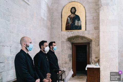 Imagen de boda en la iglesia de Puglia de tres hombres con máscaras de covid de pie al lado