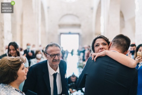 Puglia indoor church wedding photography showing the bride hugging with parents