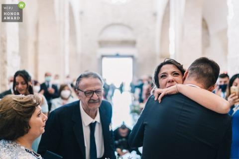 Fotografía de boda en la iglesia interior de Puglia que muestra a la novia abrazándose con los padres