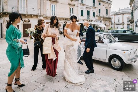 La novia y las asistentes de Puglia llegan mientras son azotadas por fuertes vientos