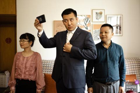 Immagine del matrimonio nel Guangdong dello sposo che si controlla per assicurarsi che tutto sia perfetto per la cerimonia, con i suoi genitori su entrambi i lati