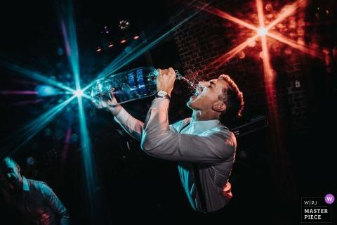 Uno sposo tedesco, molto assetato, prende un drink da una grande bottiglia di liquore a un ricevimento allo Zweigwerk 11 - Eislingen