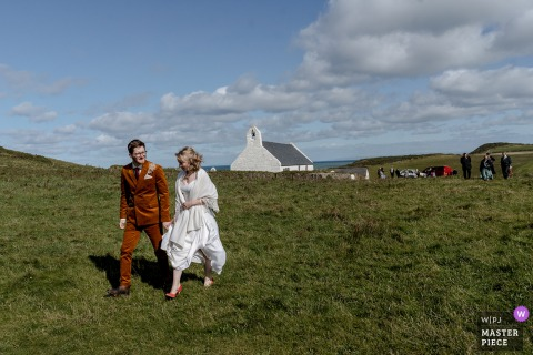 Bride and groom lead the way after their marriage ceremony at this cliff top church in West Wales at the Mwnt Church
