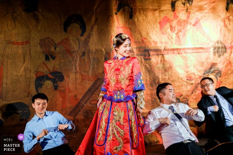 Wedding image of a bride dancing in a phoenix robe during her reception at a banquet hall in Taiwan