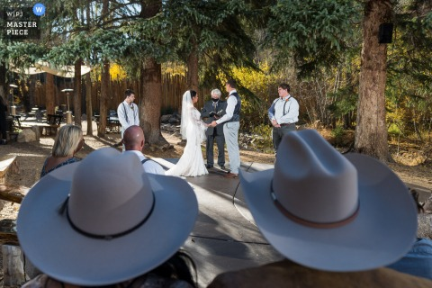 Colorado wedding image shot through cowboy hats at the ceremony in this outdoor ceremony