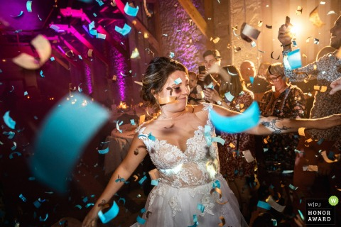 Photographie de mariage en France depuis le lieu de réception montrant la mariée arrive sur la piste de danse sous les confettis