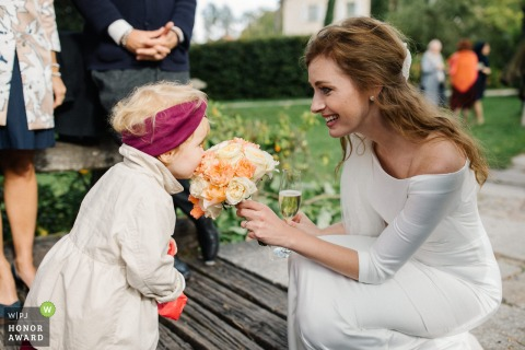 Germany outdoor wedding photography from Schloß Amerang showing the Little girl smelling the bride's bouquet