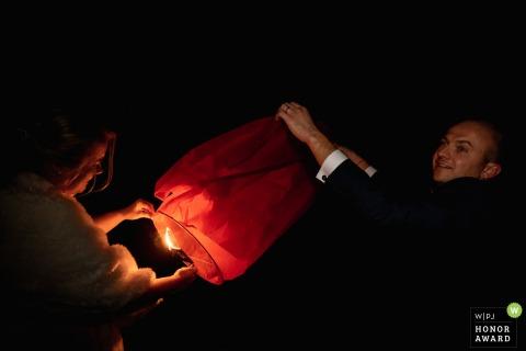 Photographie de mariage de nuit en français depuis le lieu de réception alors que les mariés préparent une lanterne thaïlandaise