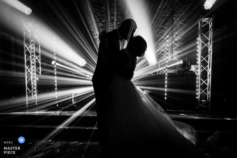 French black and white wedding photo of the bride and groom dancing with the DJ lights beaming around them