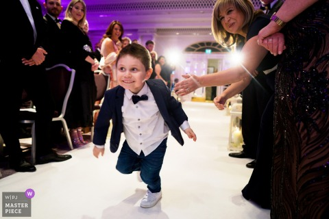 Page boy running down the aisle, arriving at the ceremony at the The Grosvenor House Hotel