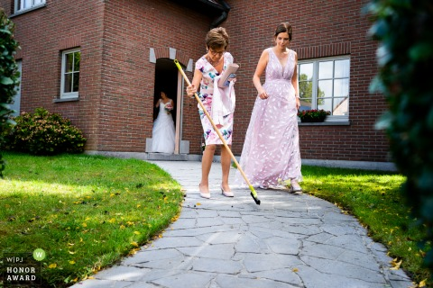 Brabant Wallon wedding photography as The bride's mother sweeps slugs away from the path where her daughter has to walk to the church