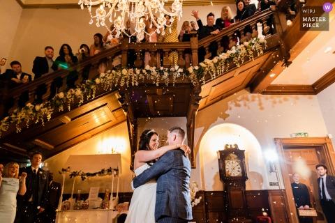 Gli sposi vengono inondati di petali di fiori dai loro ospiti all'Holmewood Hall di Peterborough
