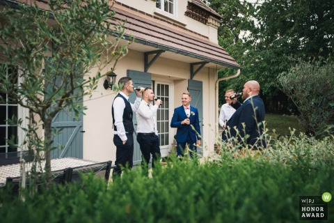 French garden wedding photo from Warluis, Oise, Hauts-de-France of the guys hanging out with drinks outside