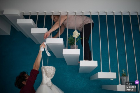Siracusa preparando a fotografia do casamento do vestido da noiva pendurado na escada interna