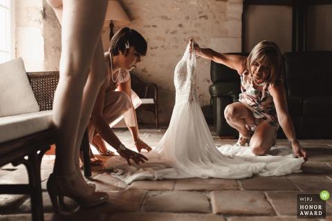 Französische Hochzeitsfotografie von Gîte de Fonteneilles, Indre zeigt die Vorbereitung des Brautkleides durch ihre schöne Mutter