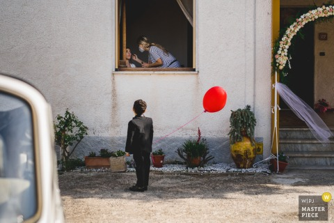 Italian wedding photo of a young child with a red balloon watching the bride have her makeup done