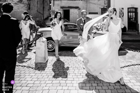 French wedding photography at the Church of Poussan South of France showing the bride walks towards the entrance of the church in a strong wind