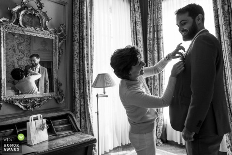 Wedding photography from Avignon Hotel la Mirande of the Groom getting ready with flower helper