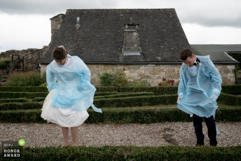 Turenne wedding photography showing the Bride and groom are wearing protection to keep their costume and dress clean