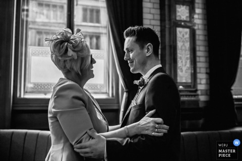 United Kingdom wedding picture of the groom with his mother embracing each other at the Manchester Town Hall