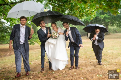 Cromac wedding picture of the bride, groom and groomsmen walking with umbrellas with the rain coming down