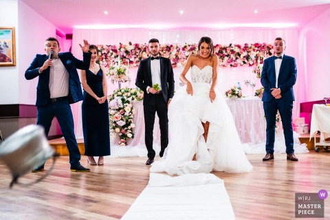 Bulgarien Hochzeitsfoto von Aglika Palace, Zhrebchevo zeigt die Reaktion der Braut und des Zeremonienmeisters, nachdem die Braut den Kupfertopf getreten hat
