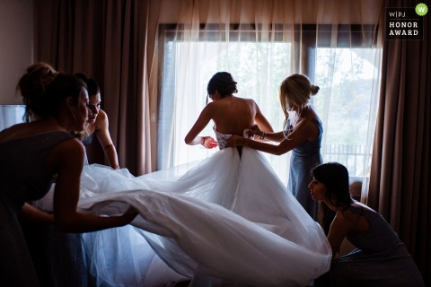 Bulgaria bridal wedding photography from Aglika Palace, Zhrebchevo showing Bridesmaids helping the Bride to put her dress on