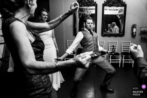 Foto di matrimonio in Colorado dalla Torre dell'orologio di Denver dello sposo che fa una faccia buffa mentre balla
