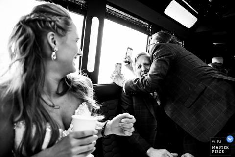 Fotografia di matrimonio di CO sulla strada per il castello di Della Terra, Estes Park con un momento divertente in limousine con festa di matrimonio