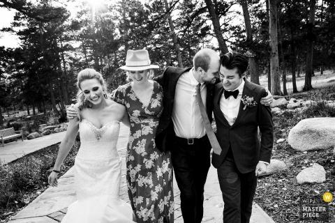 Photographie de mariage au Colorado de Della Terra Mountain Chateau, Estes Park de la mariée et le marié en descendant le chemin avec les invités du mariage