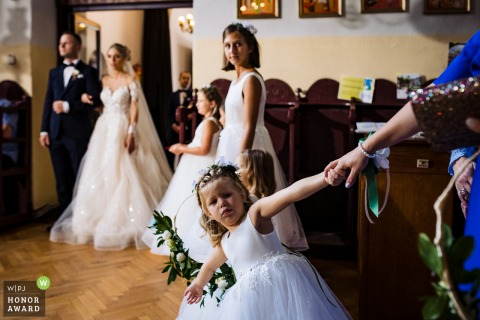 Sofia indoor wedding photography from Bulgaria created as a child pulls her mother by the hand during a ceremony at the church