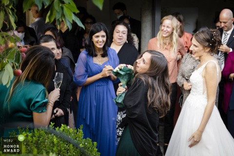 Italy garden wedding photo from Maccagno-Varese showing a Happy friend gets the bouquet from the bride