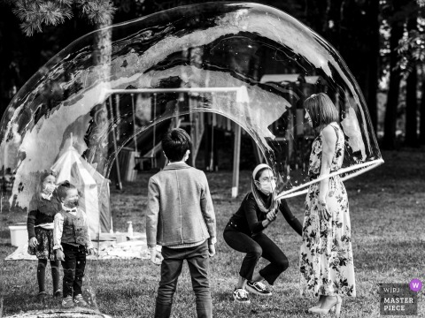 Wedding photography from the Italy Venue Chalet del Parco - Milanoshowing A guest playing with bubble soap