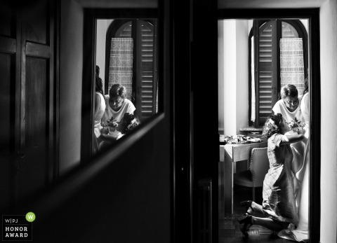 Italy black and white wedding photography from Varese at the bride's House From the corridor showing a point of view of the bride's made helping the bride to get ready