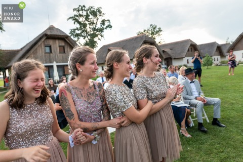 Outdoor wedding ceremony photography from Tešanovci, Slovenia showing the Bridesmaids got their laugh at the ceremony